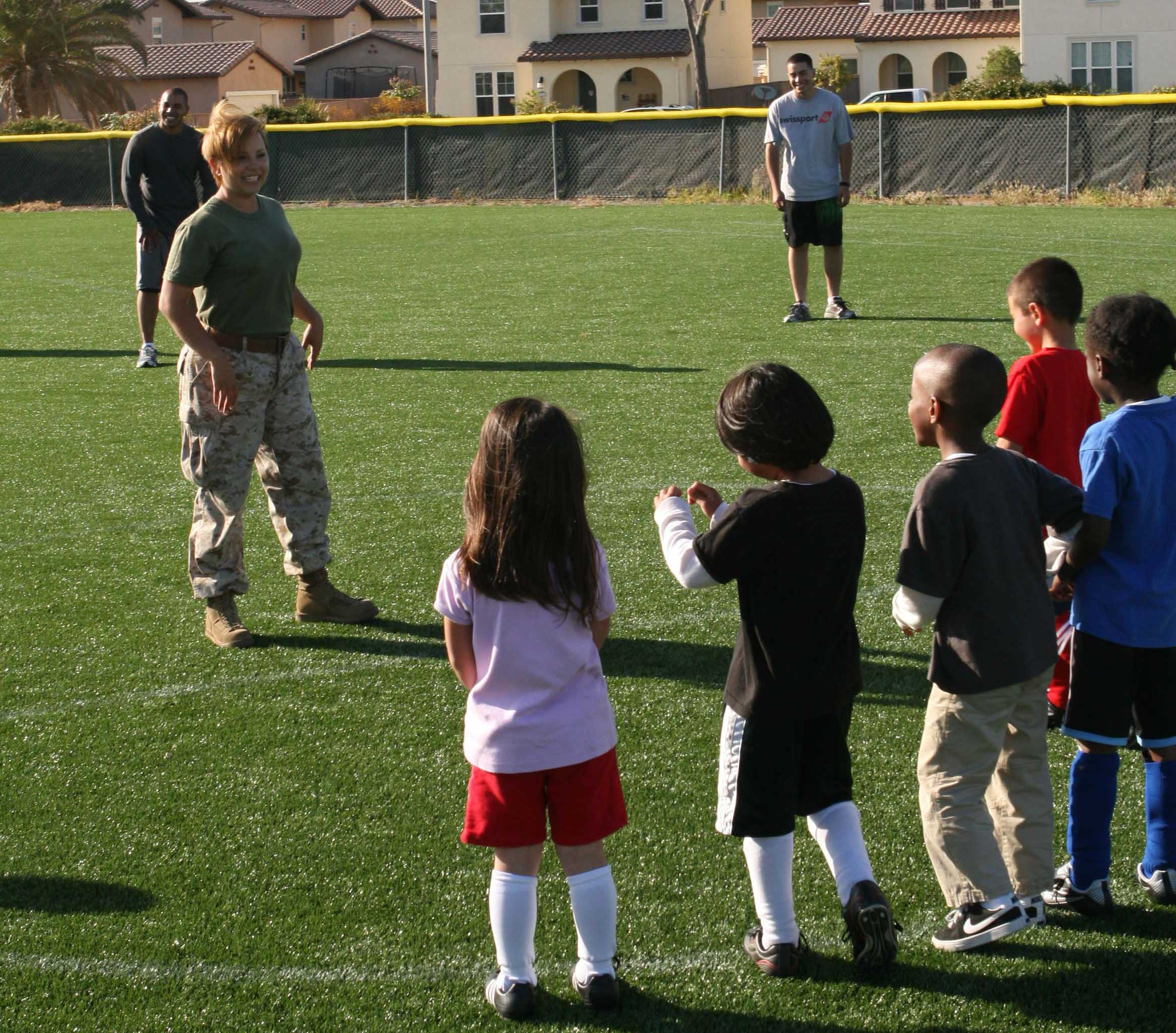 female marines in the media the semi normal day to day sgt denise serrano the combat camera photography chief headquarters squadron lines up a soccer team of five year olds for a kick at practice on